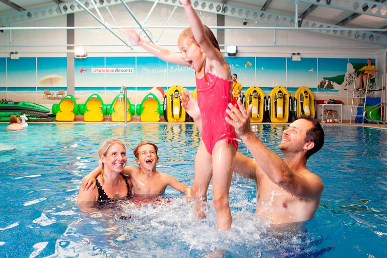 family playing in pool at Parkdean Resorts