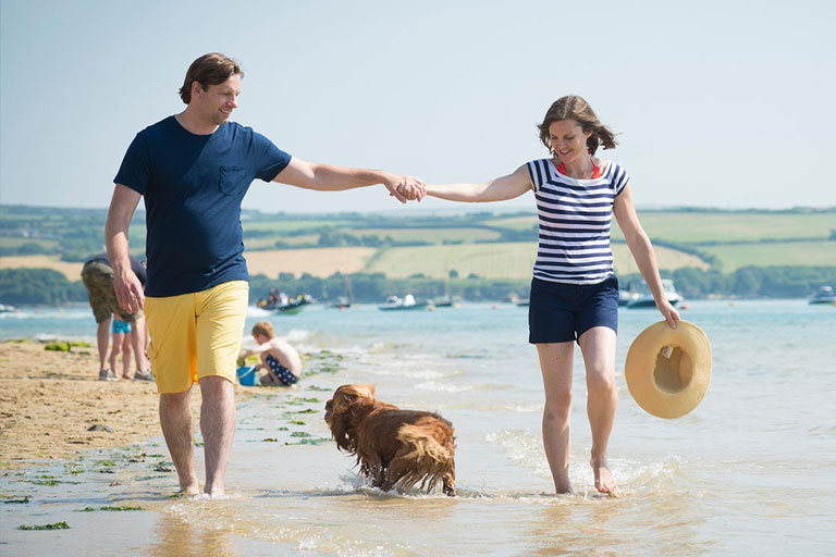 couple walking on a beach at Parkdean Resorts
