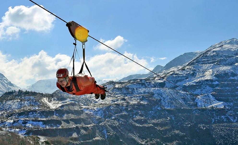zipworld man going very fast on a zipline over a lake