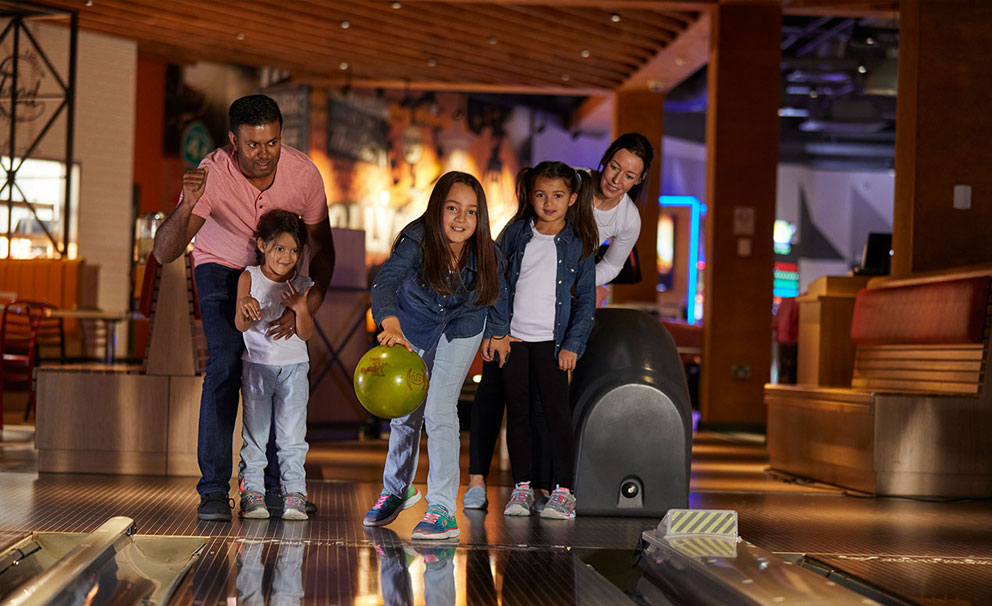 girl bowling with family